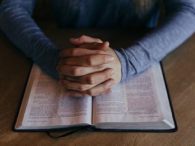 Online Biblical Studies Programs | Online Degree | Clasped hands over bible